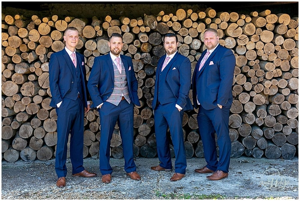 Groomsman photograph in front of logs at bury court