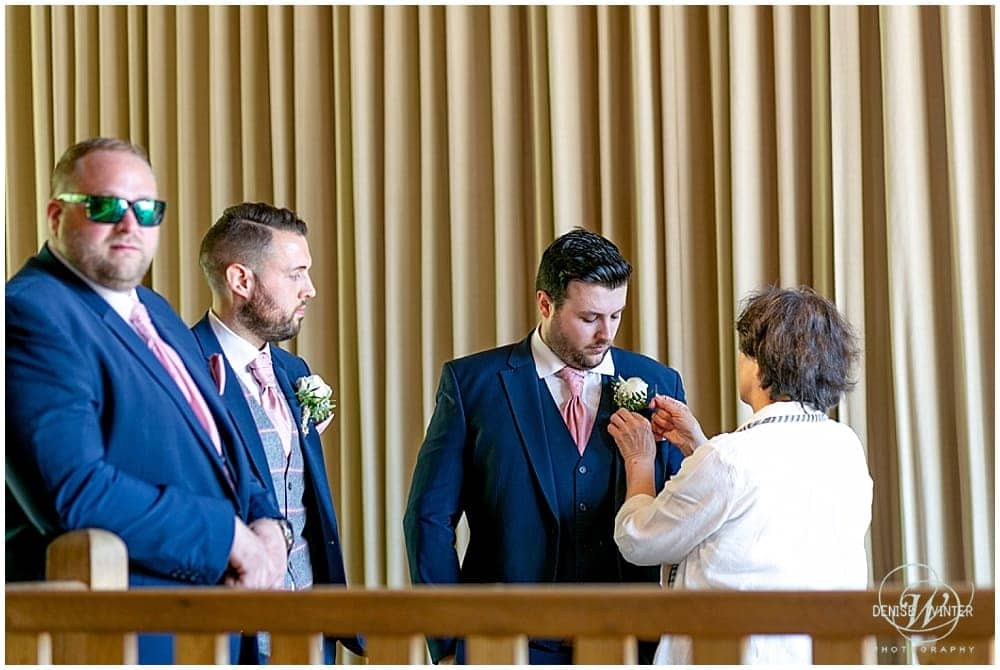 Groom having his button hole fitted