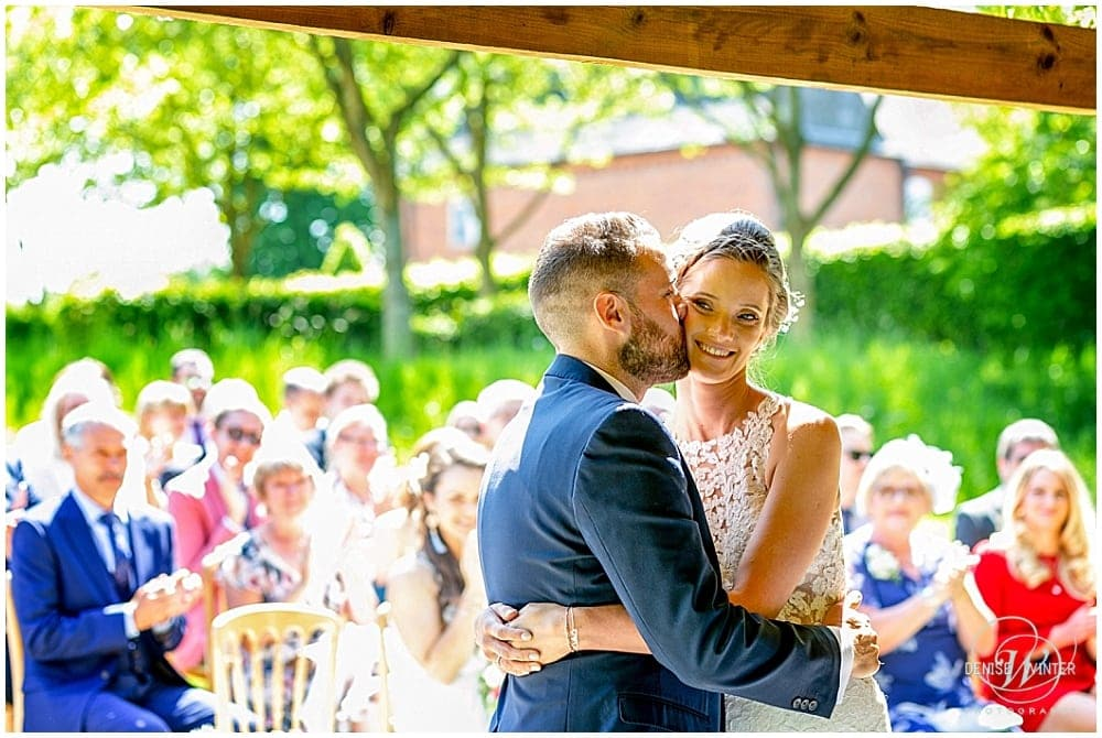 Bride and groom kiss on their wedding day