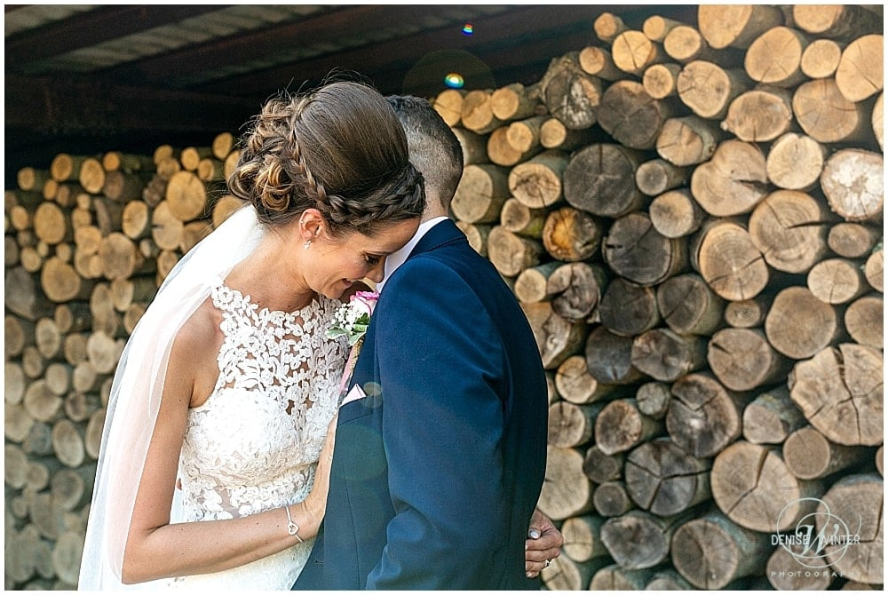 Bride ad groom picture with wooden log backdrop at Bury Court Wedding