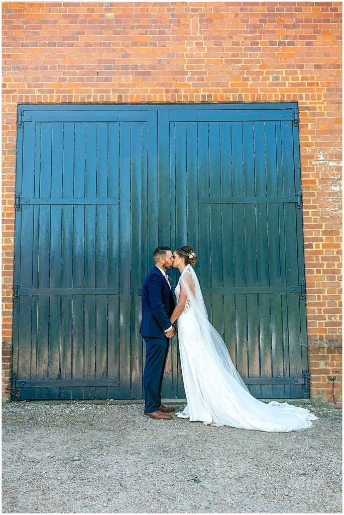 bride and groom portrait photo against a green door backdrop Bury Court Wedding
