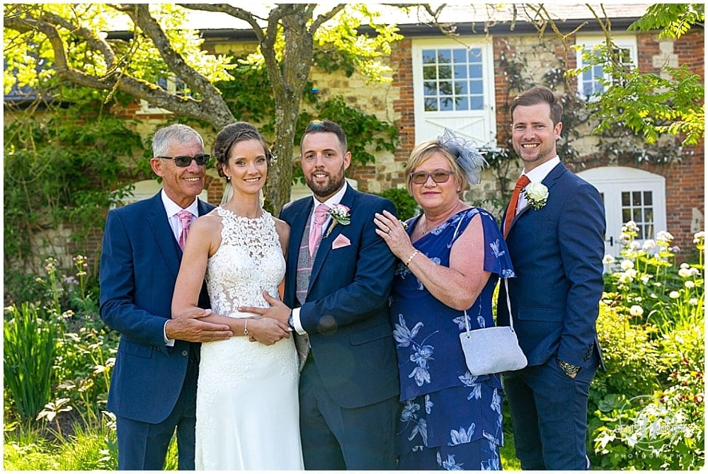 bride and groom with mum and dad at Bury Court Barn