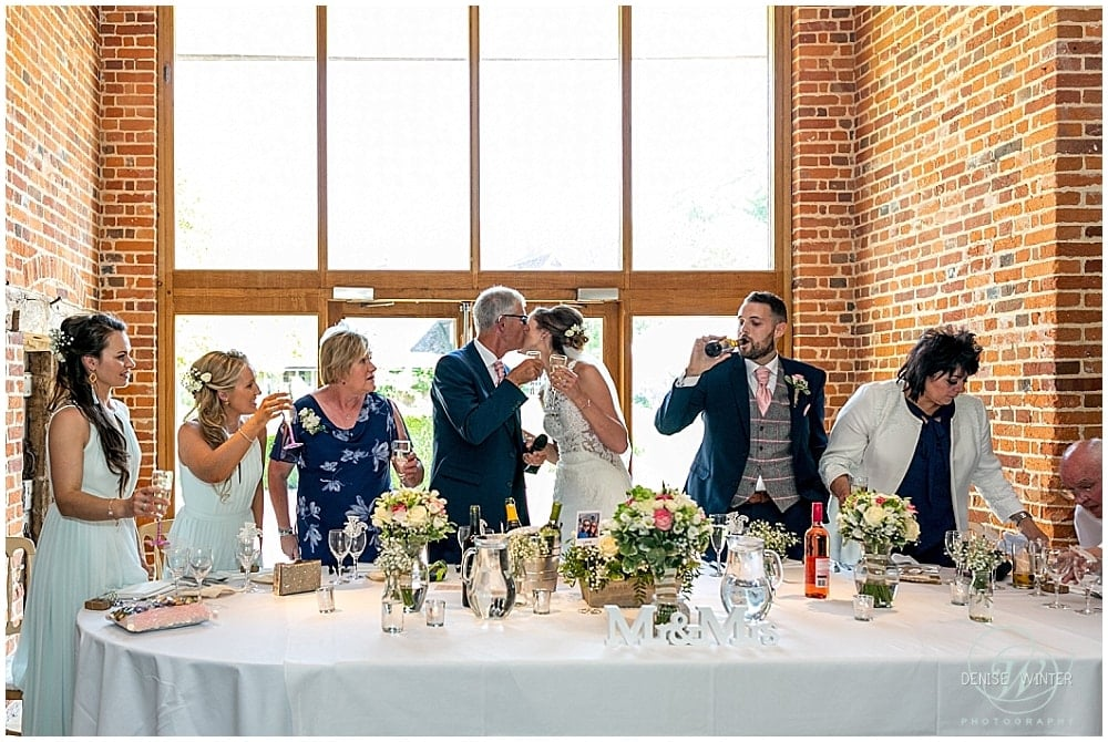 Top table speeches with bride and dad kissing and cheers