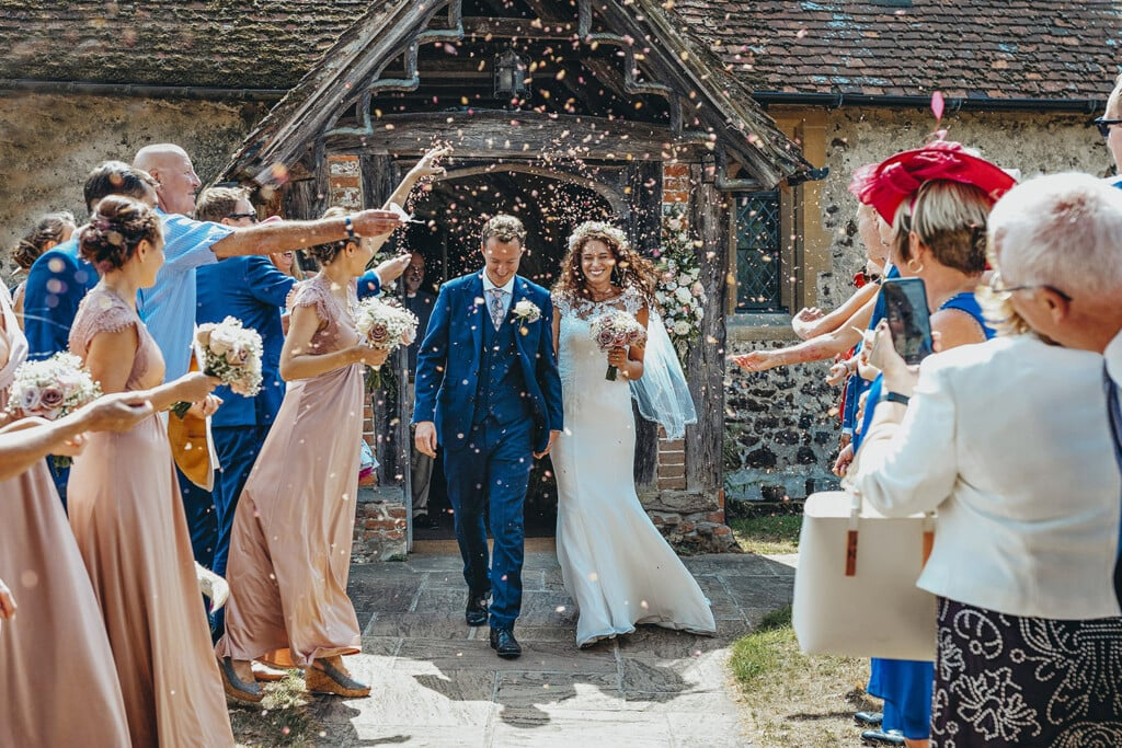 wedding photographer Surrey bride and groom leaving the church to shower of confetti