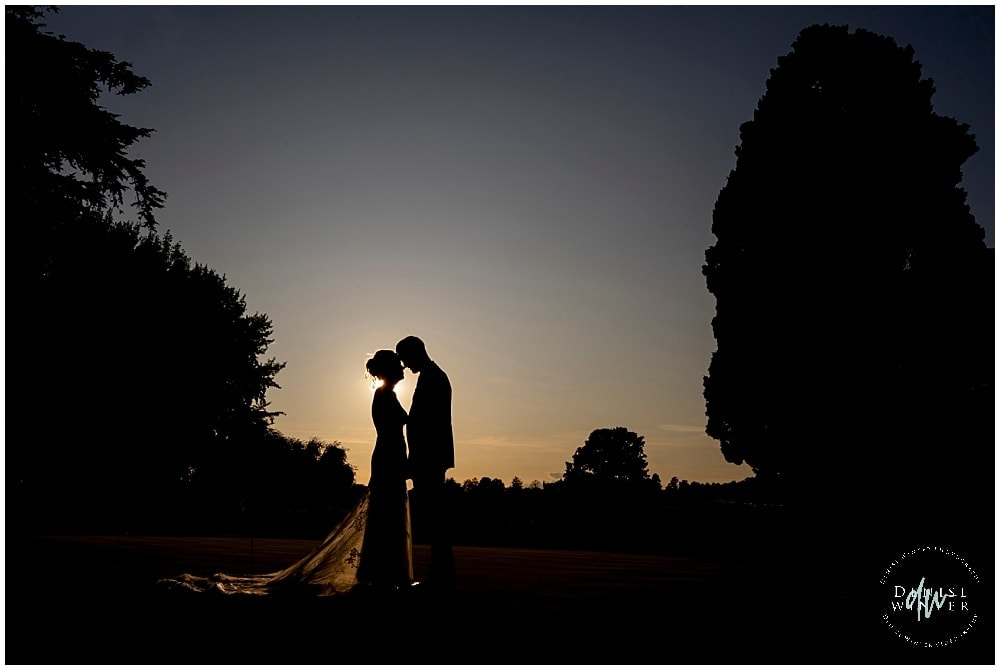 Silhouette Sunset wedding photograph with a bride and groom