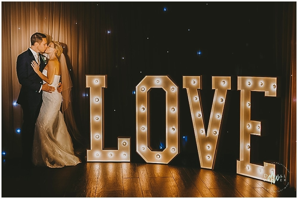 Creative lighting for wedding photo with light up love sign