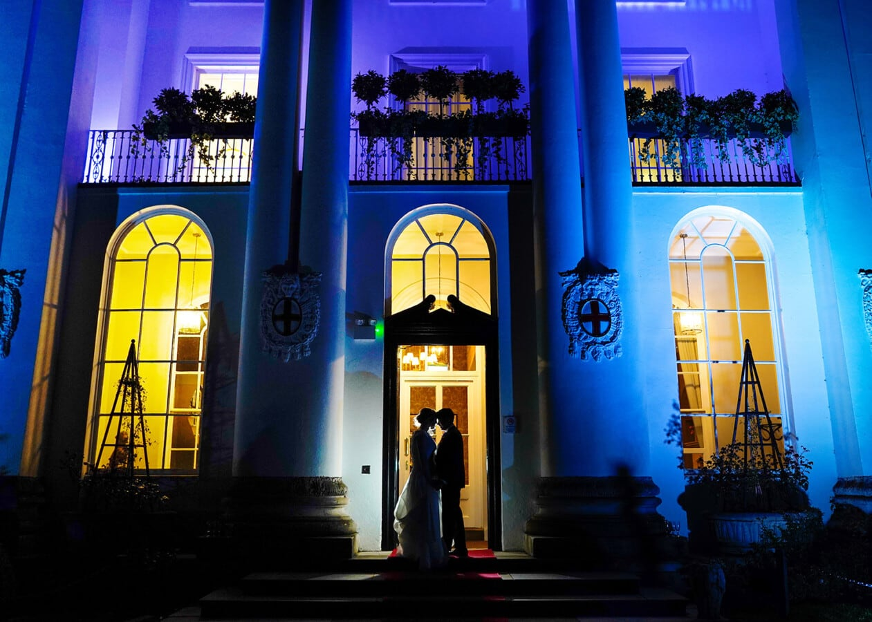 bride and groom night time photo in the doorway of beaumont estate